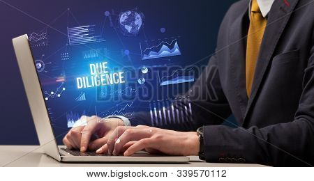 Businessman working on laptop with DUE DILIGENCE inscription, new business concept