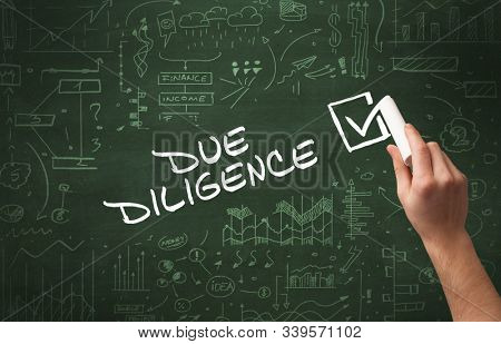 Hand drawing DUE DILIGENCE inscription with white chalk on blackboard, new business concept