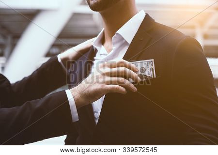 Someone Giving Bribe, Money To Businessperson Or Politician By Putting Bribe Or Cash To Suit Pocket.