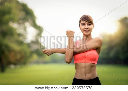 Asian Lady In Body Warm Up And Relax Flexible Action In Park On Morning Time Before Start Running, T
