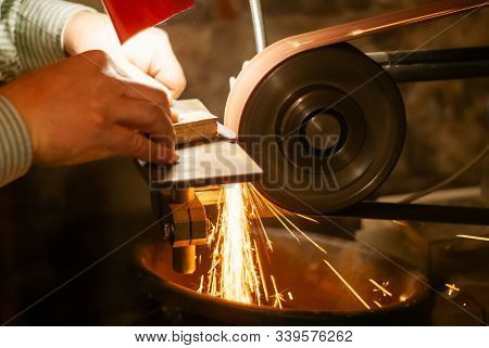 The Hands Of A Locksmith Grinding The Workpiece For A Knife On A Grinding Belt