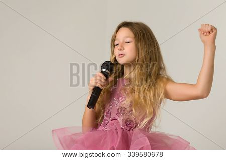 Little Girl With A Microphone. Cute Little Girl Singing With A Microphone. Karaoke. Girl Sings Joyfu