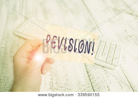 Text sign showing Revision. Conceptual photo action of revising over someone like auditing or accounting man holding colorful reminder square shaped paper white keyboard wood floor. poster