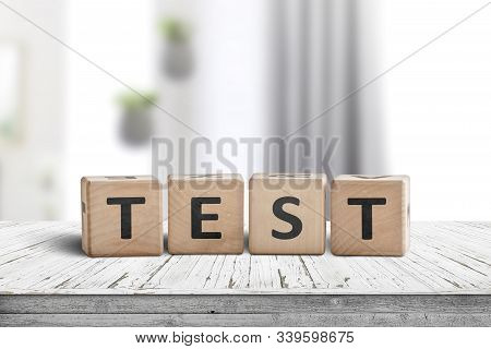 Test Sign Made Of Wood With Text In A Bright Living Room On A Desk