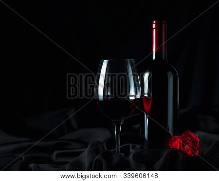 Bottle And Glass Of Red Wine On  Black Silk Background. Red Wine And Red Rose On Black Background.