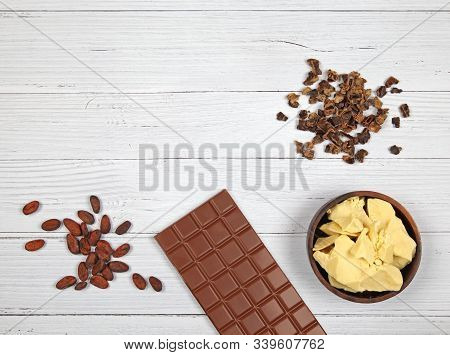 Bar Of Milk Chocolate, Carob, Cocoa Butter And Cocoa Beans On Light Wooden Background. Top View With