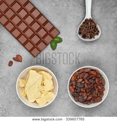 Bar Of Milk Chocolate, Cocoa Butter, Cocoa Beans, Carob And Mint On Gray Stone Background. Top View