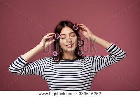 A Cute Young Girl With Dark Hair In A Striped Sweater And Pink Curlers Closed Her Eyes And Clings To