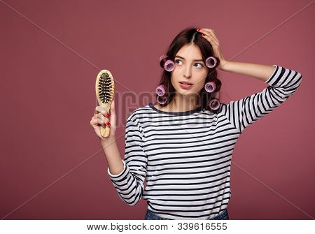 A Pensive Pretty Lady In A Striped Sweater In Curlers Stands On A Pink Background. The Lady In The C
