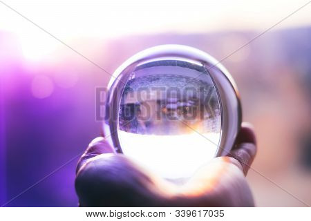 Glass Ball On Hand On Mistery Background. Abstract Glass Background. Travel And Prediction Of Future