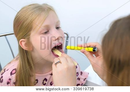 Medicine For Children And Healthcare Concept. Pediatrician Looking Child Girl Throat Using Spatula A