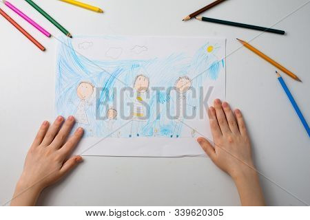 A Child Draws His Family With Pencils. Childs Drawing And Colored Pencils. Family Drawing On A White