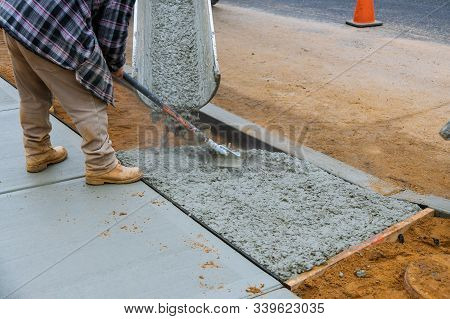 Construction Worker Pouring Reinforced Concrete Cement For Sidewalk In New Residential Home