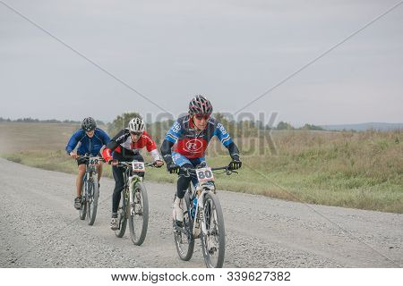 Zarinsk, Russia-september 02, 2019: Cyclists Ride On The Road Among The Woods, Ride Bicycles, Cyclis