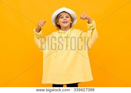 European Boy With A Panama In A Light Yellow Hoodie On A Yellow Background.