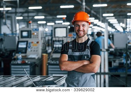 Smiling And Happy Employee. Industrial Worker Indoors In Factory. Young Technician With Orange Hard