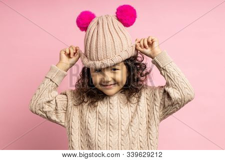 Charming Little Girl With Curly Hair Wearing Beige Sweater, Knitted Hat With Hot Pink Pom Poms Posin