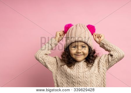 Sweet Little Girl With Curly Hair Wearing Beige Sweater, Knitted Hat With Two Hot Pink Fluffy Pom Po