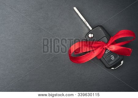 Car Key With Red Bow On Dark Black Slate Plate.