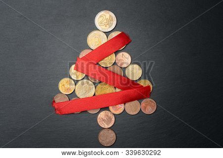 Christmas Tree Made Out Of Euro Coins With Red Ribbon Chain Or Garland On Dark Black Slate Plate Bac