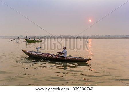 Varanasi, India - November 07, 2019: Young Man In A Row Boat On The Ganges River In Varanasi, India