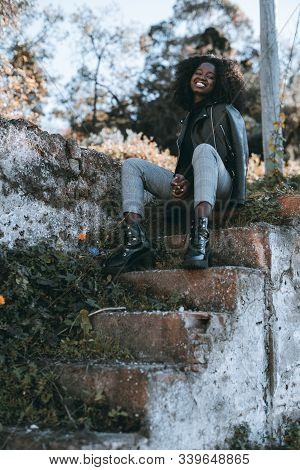 Smiling African Female In A Leather Jacket Is Sitting On Antique Stony Steps Outdoors; A Vertical Sh