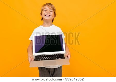 European Boy Holds Laptop Screen Forward With Mockup On Orange Studio Background With Copy Space.