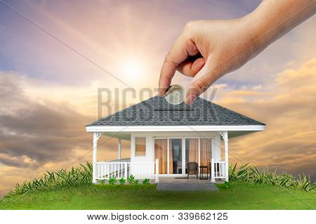 The Hands Of A Businessman Hold Money And The Other Hand Holds A House. The Idea Of Saving Money To
