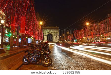 The Triumphal Arch And Champs Elysees Avenue Illuminated For Christmas 2019 . The Motorbikes In The