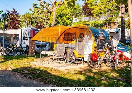 Camping La Ca, Garda Lake, Lombardy, Italy - September 12, 2019: Modern Round Yellow Gray Camper Wit