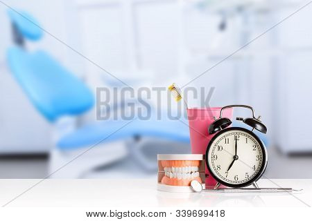 Dental Mirror And Dental Explorer Instrument Near Human Jaw, Alarm Clock And Toothbrush In Pink Glas