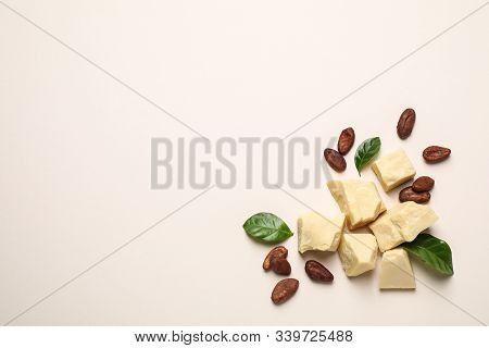 Organic Cocoa Butter And Beans On Beige Background, Flat Lay. Space For Text