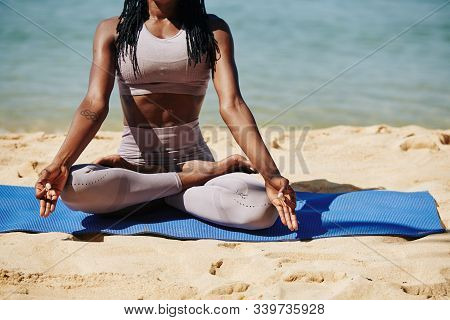 Cropped Image Of Young Black Woman In Sports Leggings Sitting On Beach In Lotus Position And Enjoyin
