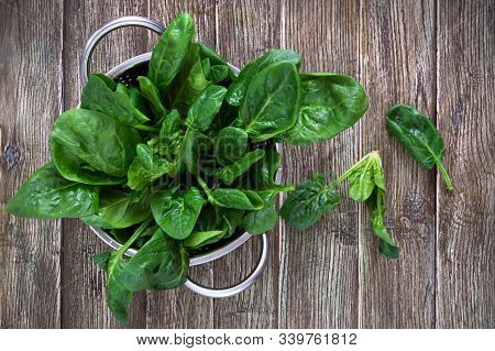 Fresh Spinach Leaves In A Bowl On A Wooden Table. Useful, Tasty, Low-calorie Greens. Young Spinach S