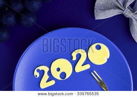 Figures 2020 Made Of Cheese With Holes On Blue Plate With Small Fork On Empty Table With X-mas Decor
