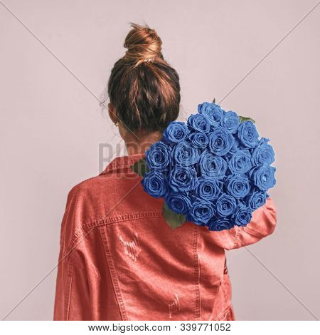 Back View Of Young Woman In Pink Coral Denim Jacket Holding Bunch Of Blue Roses On Shoulder. Girl Wi