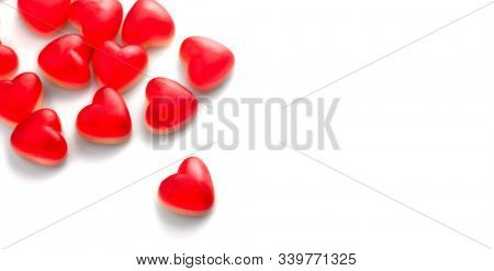 Heart shaped jelly candy, love background. Red jelly sweets candies on white backdrop. St. Valentines, marriage hearts border background. Closeup