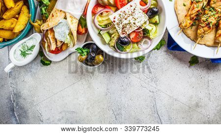 Greek Food: Greek Salad, Chicken Souvlaki, Gyros And Baked Potato Wedges On Gray Background, Top Vie