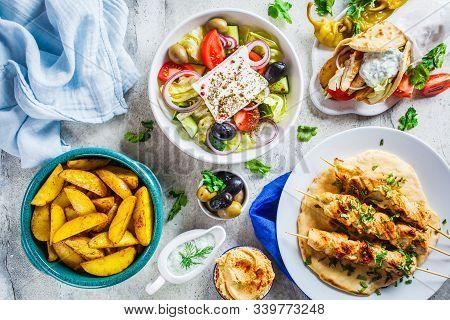 Flat Lay Of Greek Food: Greek Salad, Chicken Souvlaki, Gyro And Baked Potatoes On A Gray Background,