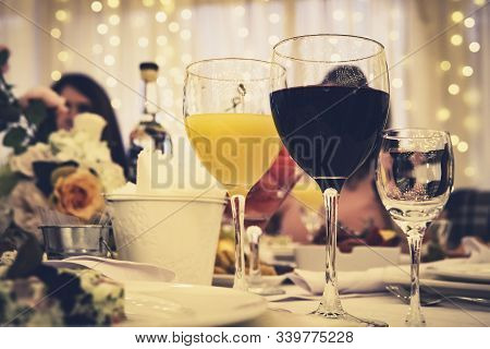 Close Up Of Stemwares On A A Served Restaurant Table At A Festive Occasion. Filled Glasses Of Red Wi