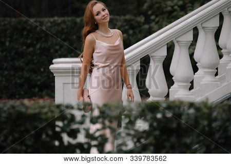 Beautiful lady in luxurious ballroom dress against Baluster railing of her palace. Vintage concept