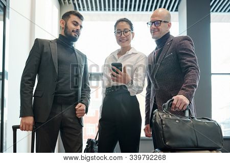 Young elegant female business traveler with smartphone and her two male colleagues searching for right way to hotel in the net