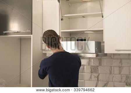 Worker Assemblying Home Range Hood In Kitchen Furniture.