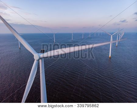 Windmill Park Green Energy During Sunset In The Ocean, Offshore Wind Mill Turbines Netherlands