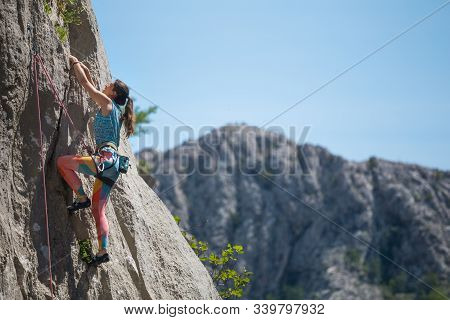 Rock Climbing And Mountaineering In The Paklenica National Park. A Woman Overcomes A Challenging Cli