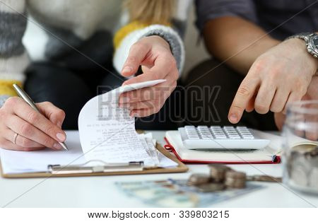 Close-up View Of Man And Woman Making Account Of Family Income. Writing Down And Calculating Expense