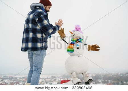 Man In Winter Clothes. Winter Holiday. Bearded Man Shakes Hand With Snowman. Santa Claus Man With Sn