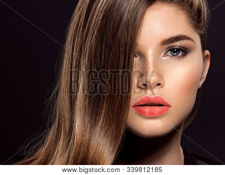 Woman with beauty long brown hair. Fashion model with long straight hair. Fashion model with a smokey makeup. Pretty woman with living coral color lipstick on lips. Living coral.