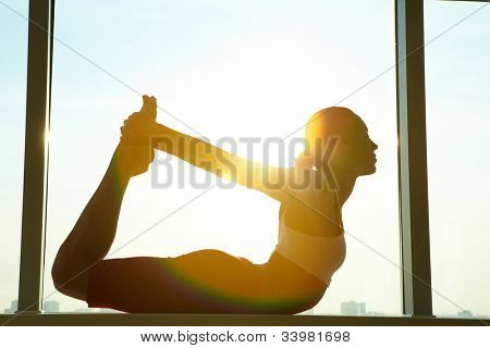 Portrait of young sporty girl doing stretching exercise