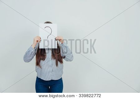 Inquisitive Asian Student Girl Hiding Her Face Behind A Sheet Of Paper With Question Mark Written On